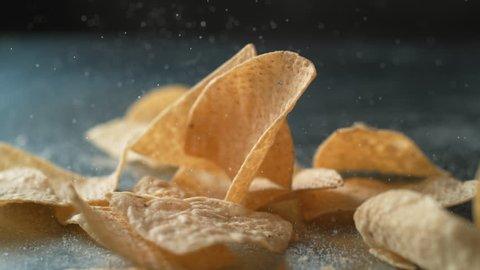 Tortilla chips sprinkled with salt. Shot with high speed camera, phantom flex 4K. Slow Motion.