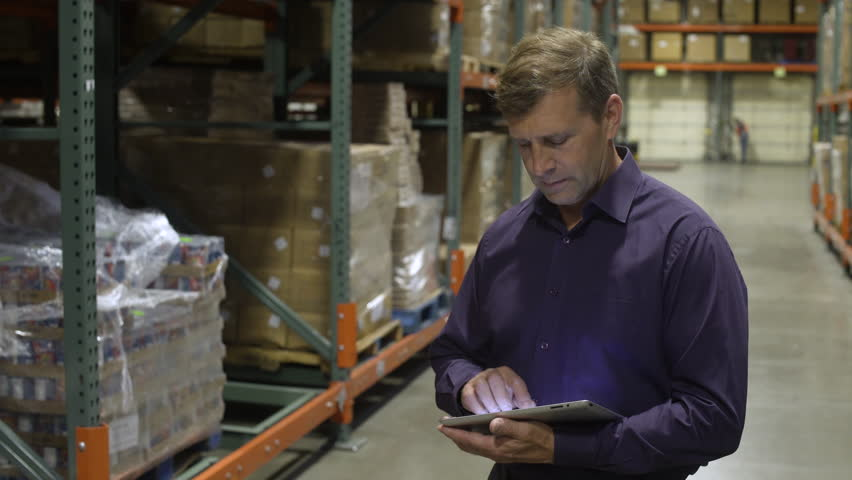 Mid adult man using a tablet in a warehouse | Shutterstock HD Video #1011043817