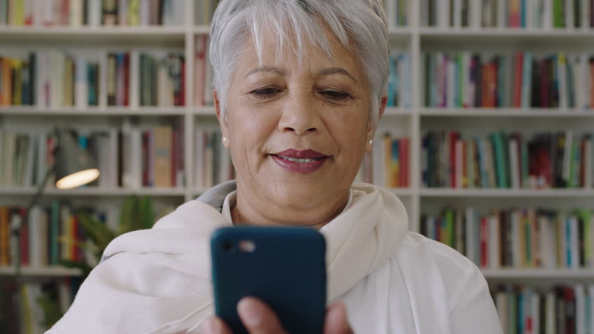 Portrait of friendly indian middle aged woman teacher laughing standing in library using smartphone sharing social media texting using smartphone digital touchscreen technology | Shutterstock HD Video #1011075737