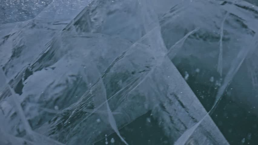 Snow is flying over surface of ice. Snowflakes fly on ice of Lake Baikal. Ice is very beautiful with unusual unique cracks. Snow sparkles and glows in red. Shooting slow motion 180fps. Picture at