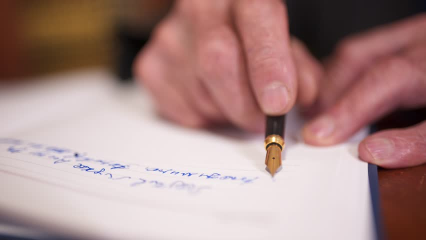 Close up of old man writing with pen. Elderly gentleman uses pen with ink to write on paper, at his home.