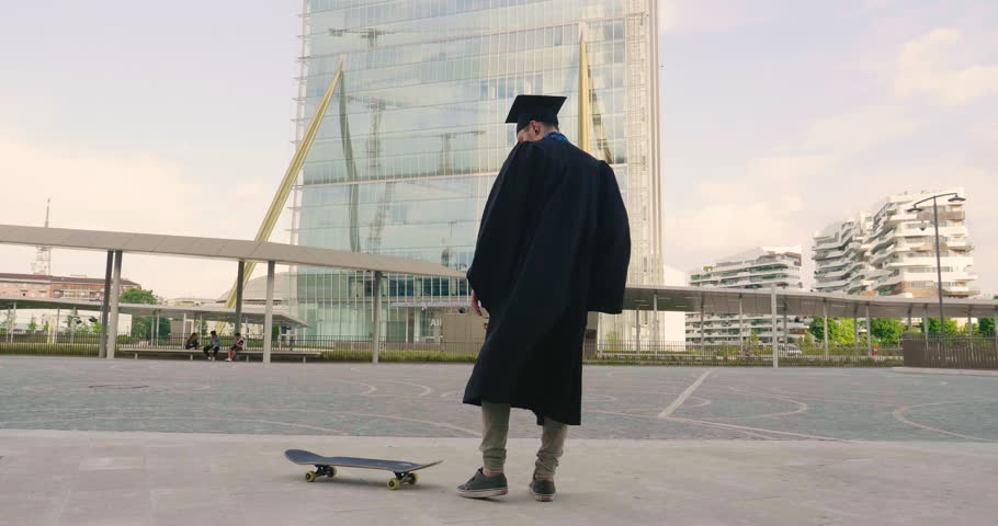 A university student has just graduated and goes skateboarding with a graduate toga and performs tricks in the middle of the city between buildings and skyscrapers. Concept of: educational, student