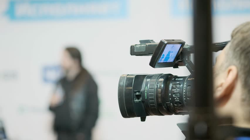 Videocamera keeps record of performance of lecturer in presentation hall. | Shutterstock HD Video #1011119807