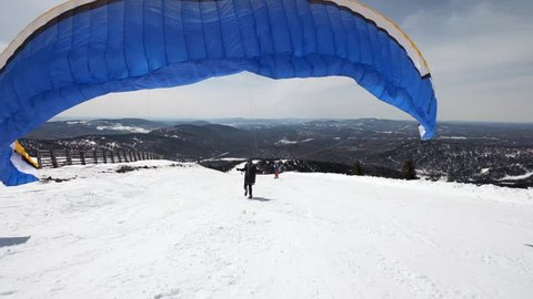 raises the sail wing of the paraglider. He starts to take off, breaks away from the ground, runs away. Paragliding in winter. Slow motion