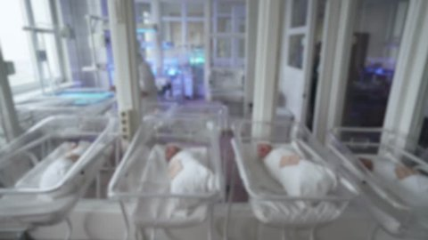 Blurred view of interior maternity hospital, newborn babies in cots.