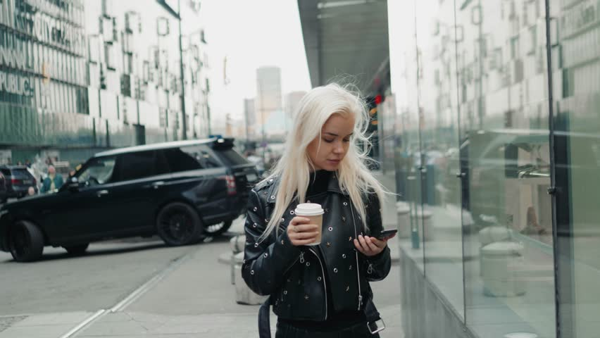 Photo of smiling young lady wearing sunglasses walking outdoors with coffee chatting by mobile phone. Looking aside. #1011155027