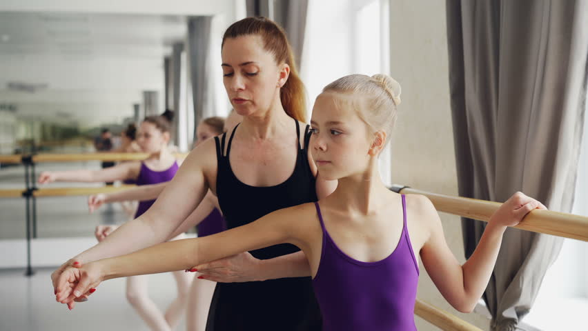 Experienced ballet teacher is teaching young female students ballet movements and positions while diligent girls are dancing moving arms and doint plie holding bar.