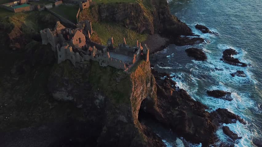 Aerial view of Dunluce castle on a cliff during sunset, Northern Ireland | Shutterstock HD Video #1011168257