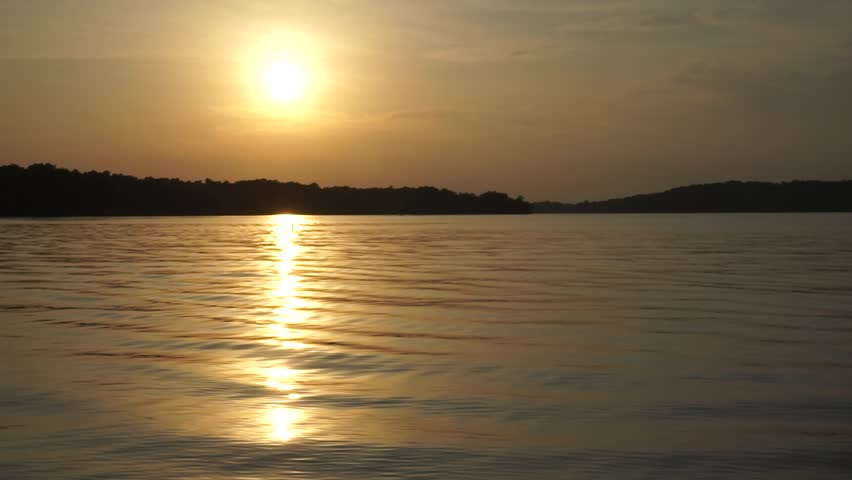 amazing view at Barkley lake in Kentucky with ripples across water and awesome and beautiful warm sunset over the horizon.  boating and camping views under the stars.  Earth before night time.  retire