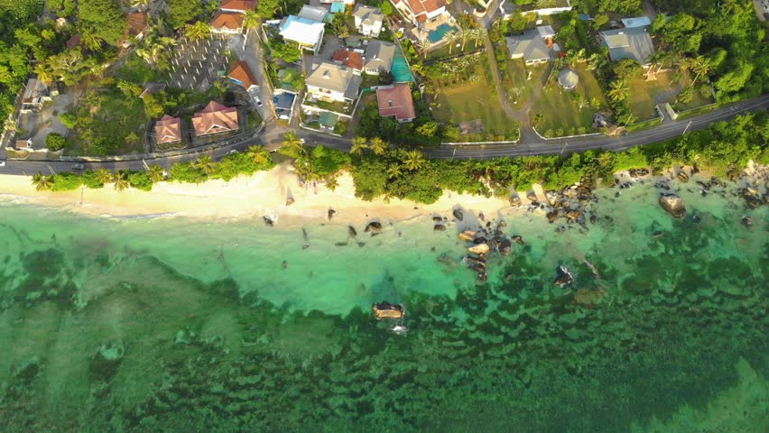 Seychelles tropical island luxury vacation, drone view at the tropical island with palm trees white sand and blue ocean Mahe Seychelles