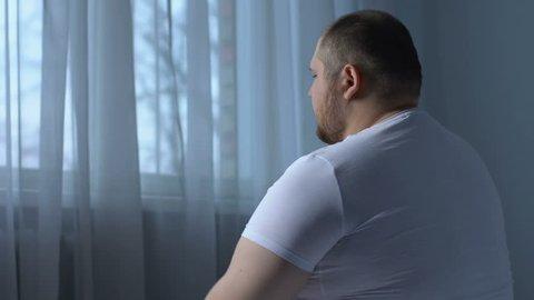 Overweight man massaging elbow joint, feeling pain, rehabilitation center client