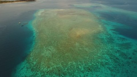 Aerial view coral reef, atoll with turquoise water in the sea.Tropical atoll, coral reef in ocean waters. 4K video. Travel concept. Aerial footage.