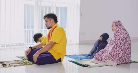 Asian muslim family praying together while wearing islamic clothes at home. Shot in 4k resolution