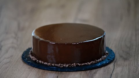 Glazing chocolate mousse cake, close-up. Cut a piece of chocolate cake with a knife.