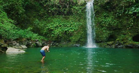 Young man dives into beautiful tropical waterfall, travel and adventure lifestyle