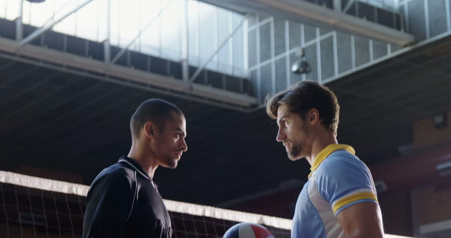 Aggressive male volleyball players looking each other through net at court 4k