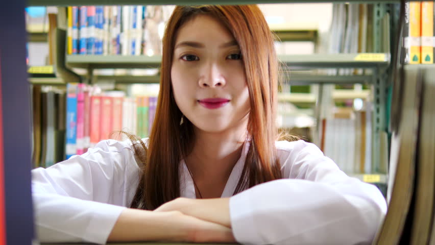 Advertising, Education, Business, Healthcare, Medical Concept - Beautiful young asian medical doctor standing near bookshelves in modern interior library. Bookshelves in background.  | Shutterstock HD Video #1011280247