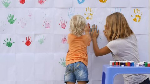 A little cute happy funny child painting color handprints on the white wall with smiling mother together and giving five by hands in print 50fps