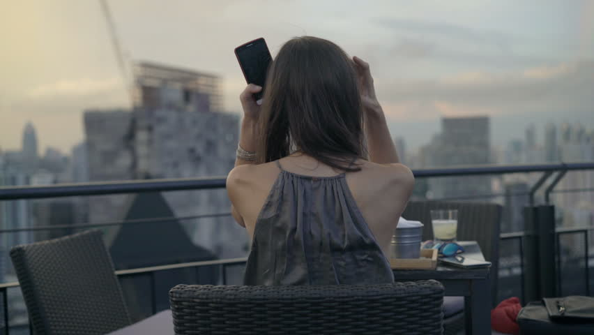 Young woman drinking cocktail sitting in skybar  | Shutterstock HD Video #1011288377