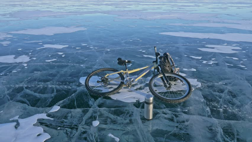 Man and his bicycle on ice. He looks at the beautiful ice in the cracks. First-person view. The cyclist is dressed in a gray down jacket, backpack and helmet. Ice of the frozen Lake Baikal. The tires   Shutterstock HD Video #1011305537
