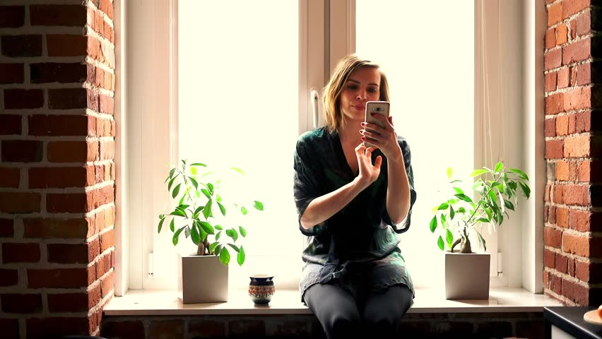 Young, pretty woman in bathrobe taking selfie photo by window at home.   | Shutterstock HD Video #1011319277