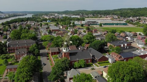 A forward aerial establishing shot of a Pennsylvania small town's business and residential districts. Ohio River in the distance. Pittsburgh suburbs.