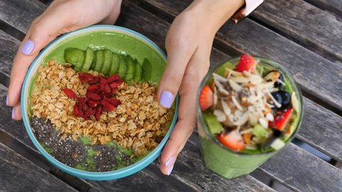 Woman Hands Holding Vegan Avocado Smoothie Bowl For Healthy Breakfast.
