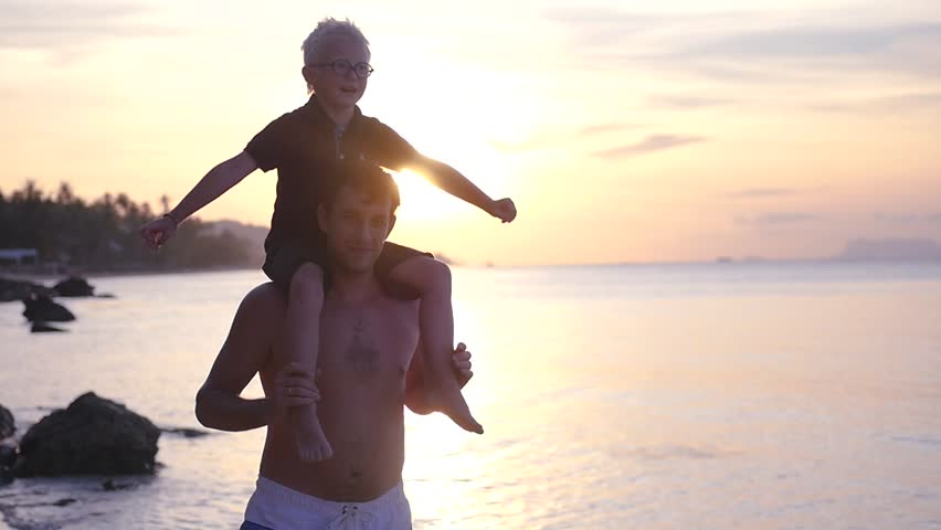 The son of a blond albino, sits on his father's shoulders, arms outstretched against the backdrop of a sunset at sea. slow motion, 1920x1080, full hd #1011330407
