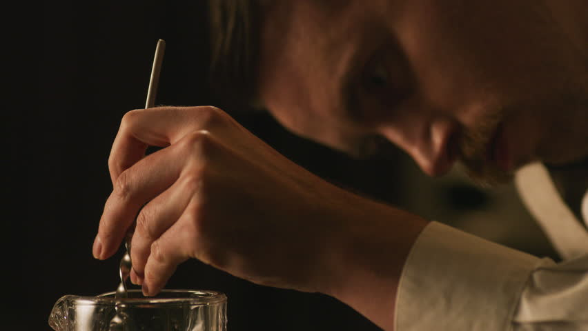 Close up of bartender stirring negroni for cocktail. Restaurant cinematic scene. Shot with a RED camera.