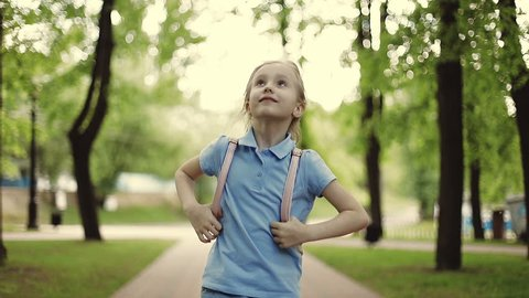 A sweet school girl in shorts is jumping in the park. A beautiful child with a backpack is walking in the summer. Slow motion.