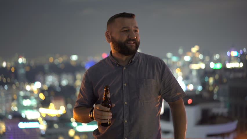 Portrait of happy man talking and raising toast with beer in skybar at night  | Shutterstock HD Video #1011354227