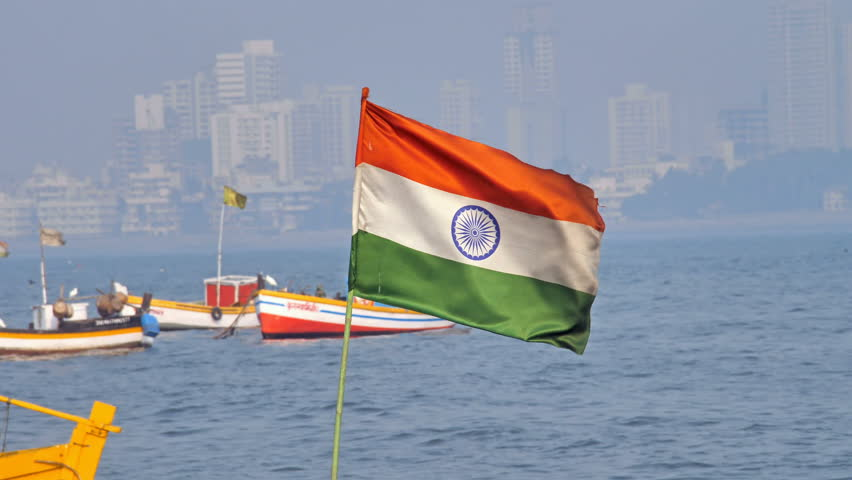 Indian national flag mounted on a small fishing boat waving on windy day. Indian flag is waving in a Arabian sea while vibrant city skyline is visible in the background, Mumbai, India