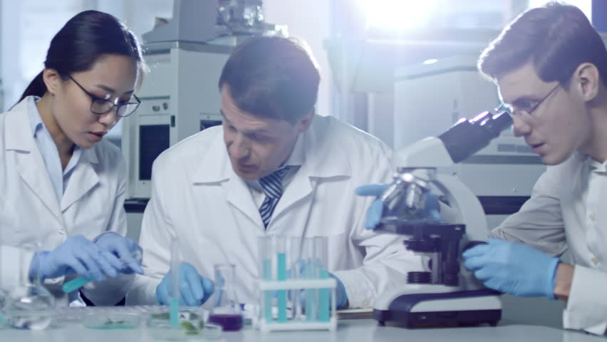 Tracking shot of three scientists working in laboratory and conducting experiments with test tubes and microscope | Shutterstock HD Video #1011374837