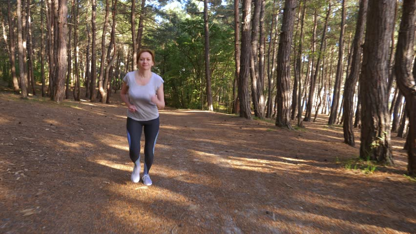 Woman running away on a trail in the sunny summer forest. motivation for sports activity outdoors, training and exercising in beautiful nature. solar glare, slow-motion 4k, steadicam shot #1011380897