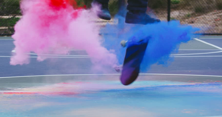 Skateboarder does extreme flip trick with colored powder in slow motion