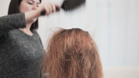 Attractive young hairdresser drying her clients red hair with a hairdryer and brushing it. Locked down real time medium shot