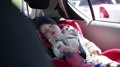 one-year-old child sleeping in a car seat.