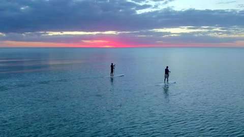 Two Paddleboarders with Pink Sunset by Aerial Drone