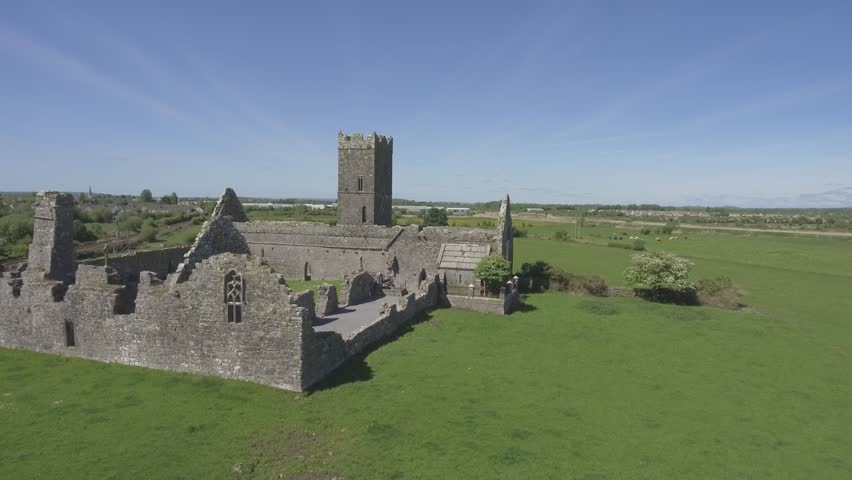 Beautiful scenic aerial birds eye view old ruins of Clare Abbey in County Clare, Ireland. Irish rural countryside with old Irish religious Abbey in decay.