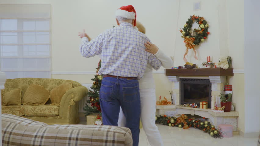 Mature man wearing santa hat dancing with wife at home near Christmas tree | Shutterstock HD Video #1011438767