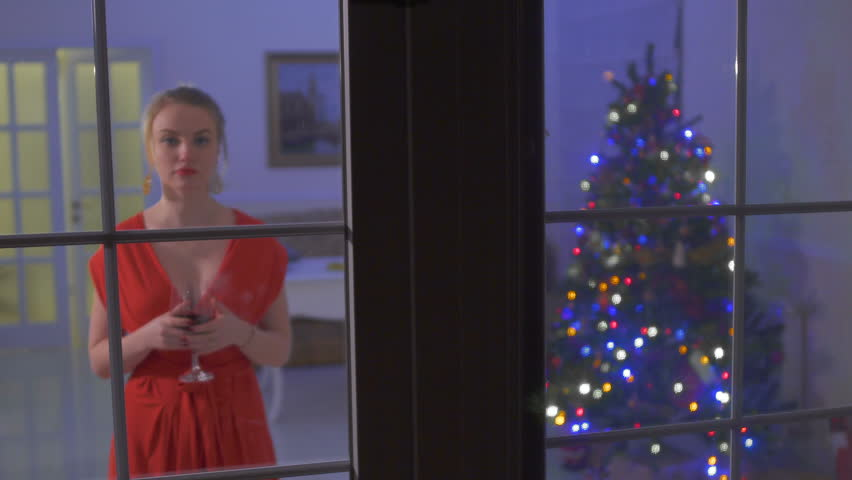 Beautiful woman in red dress with big decollete look at dark window