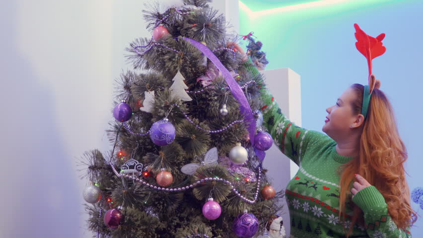 Girl look Christmas tree decoration and play with long hair | Shutterstock HD Video #1011439187