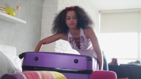 Worried young black woman packing bags for holiday. Upset latina girl ready for traveling, falling to the ground trying to lift heavy suitcase.