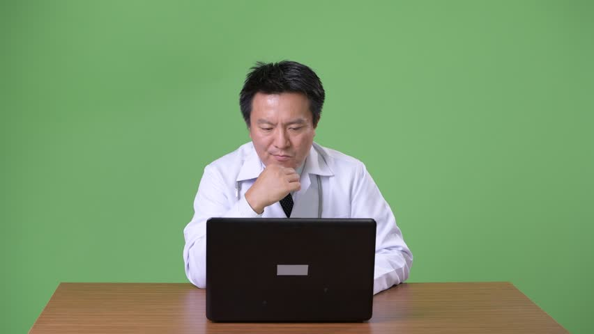 Mature Japanese man doctor against green background | Shutterstock HD Video #1011457127