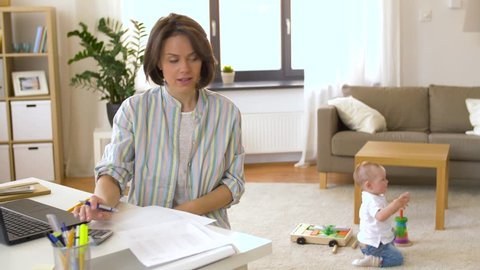 multi-tasking, freelance and motherhood concept - working mother with baby boy at home office