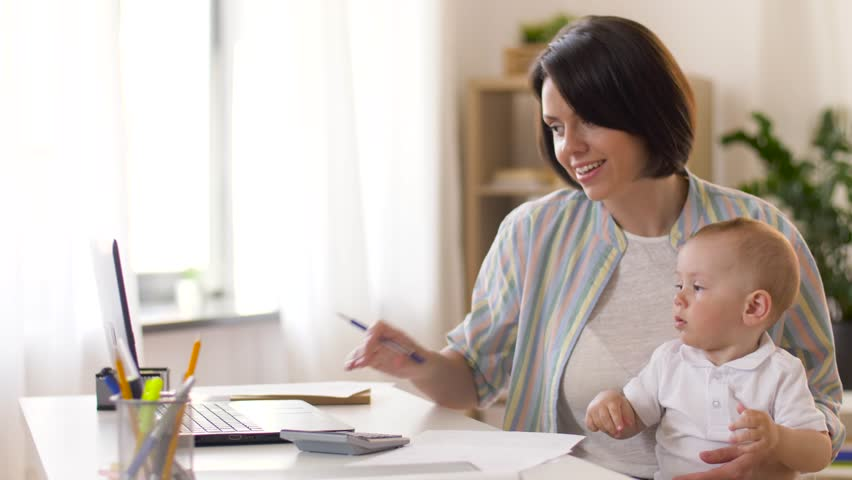 Multi-tasking, freelance and motherhood concept - working mother giving pen to baby boy at home office