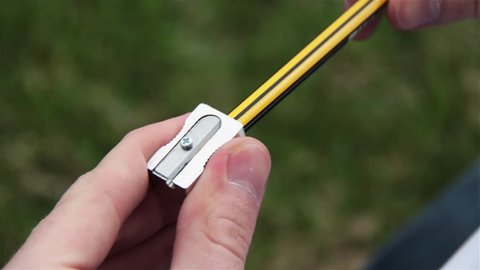Male Hands Sharpening A Pencil Using A Pencil Sharpener. Filmed Outside. Zoom In.