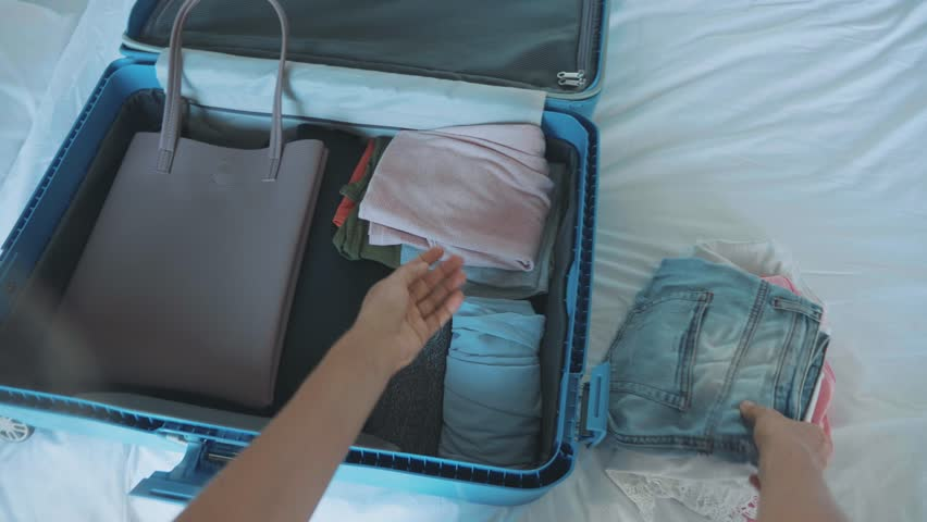 Young woman is collecting a suitcase. The traveler preparing for journey. | Shutterstock HD Video #1011467057