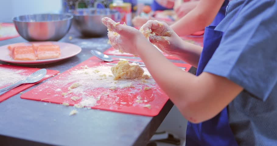 Close-up of a child's hands as he prepares a dough in the kitchen | Shutterstock HD Video #1011485387