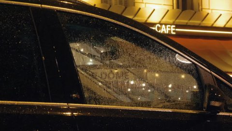 Cinemagraph - Car parked near the cafe in the city in rainy evening. Wet automobile with windscreen wipers working